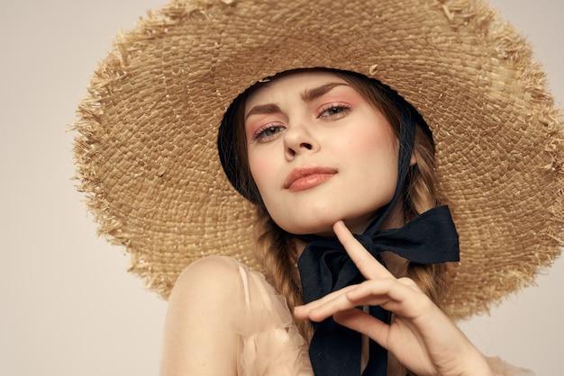 Jovem garota em um vestido transparente e com um chapéu, uma boneca viva