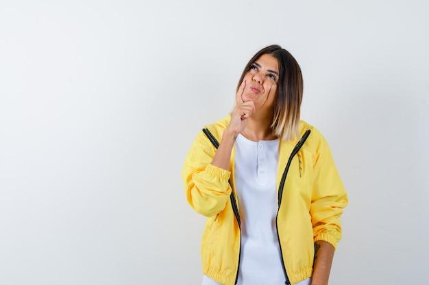 Jovem garota em uma camiseta branca, jaqueta amarela, apoiando o queixo na palma da mão, pensando em algo e parecendo pensativa, vista frontal.