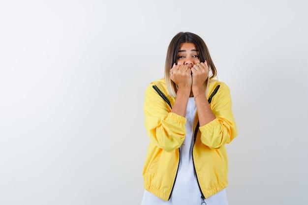 Jovem garota em uma camiseta branca, jaqueta amarela, mordendo os punhos emocionalmente e parecendo assustada, vista frontal.