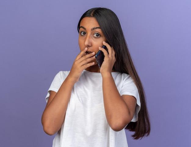 Jovem garota em uma camiseta branca parecendo surpresa enquanto fala no celular