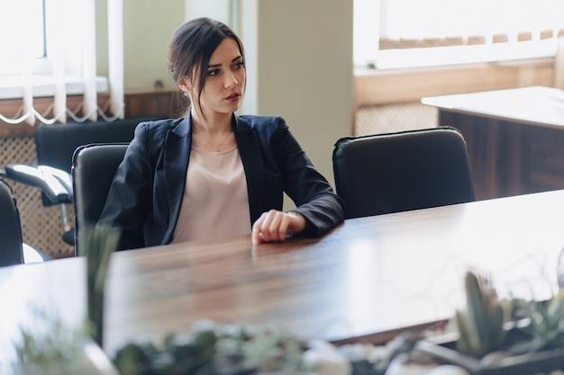 Jovem garota emocional atraente em roupas de estilo empresarial, sentado na mesa com telefone no escritório ou audiência