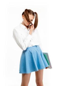 Jovem garota emocional em uniforme posando, isolado na parede branca