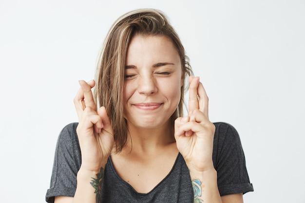 Jovem garota emotiva bonita rezando com os olhos fechados.