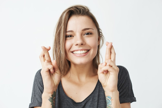 Jovem garota emotiva bonita rezando sorrindo.