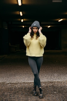 Jovem garota encaracolada com suéter amarelo e boné cinza fica sozinha nas luzes da cidade