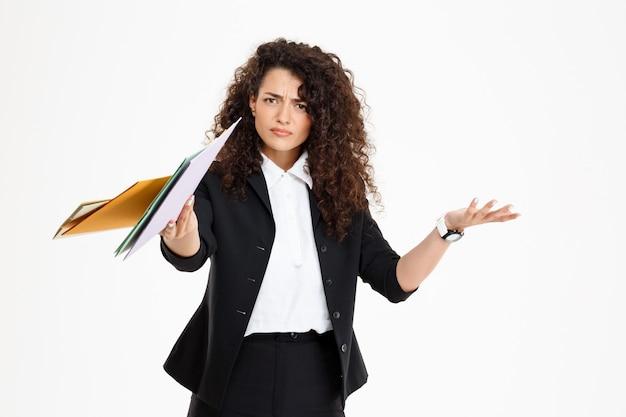Jovem garota encaracolada confusa segurando documentos