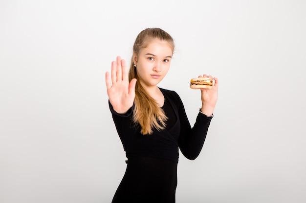 Jovem garota esbelta mantém um hambúrguer e uma maçã contra uma parede branca. escolhendo comida saudável, sem fast-food, espaço para texto