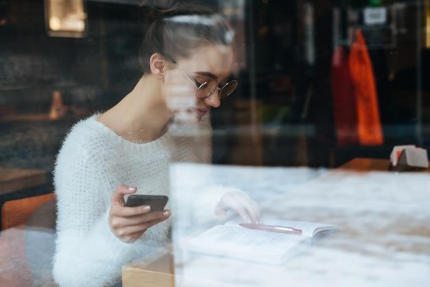 Jovem garota esperta de suéter branco e óculos sentada em um café, trabalhando, olhando para o caderno