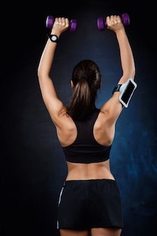 Jovem garota esportiva bonita treinando com halteres sobre parede escura.