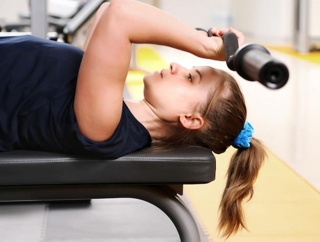 Jovem garota esportiva em roupas esportivas deitada sobre equipamentos de fitness, treinando com halteres na academia