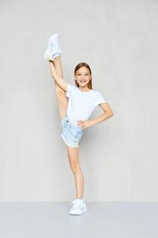 Jovem garota esportiva em shorts jeans e camiseta posando no estúdio