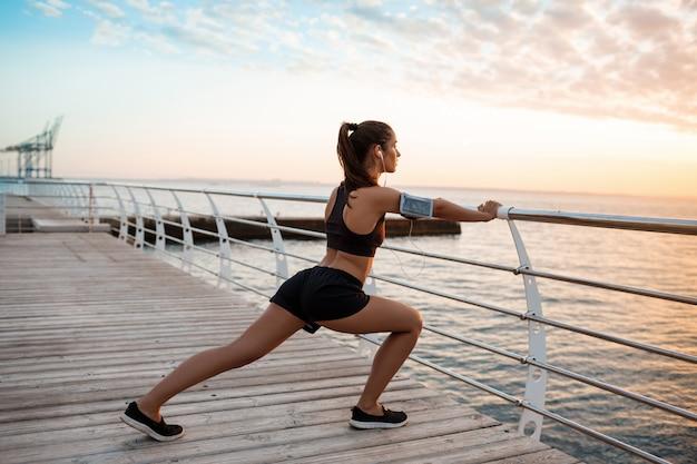 Jovem garota esportiva linda formação ao nascer do sol sobre a beira-mar.