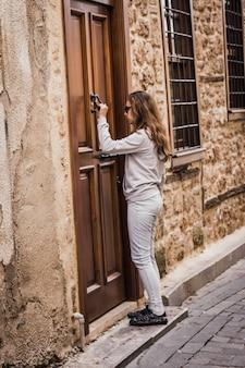 Jovem garota está batendo em uma porta de madeira velha na rua estreita da cidade velha em antalya
