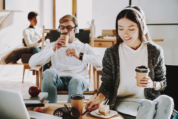 Jovem garota está bebendo café em fones de ouvido