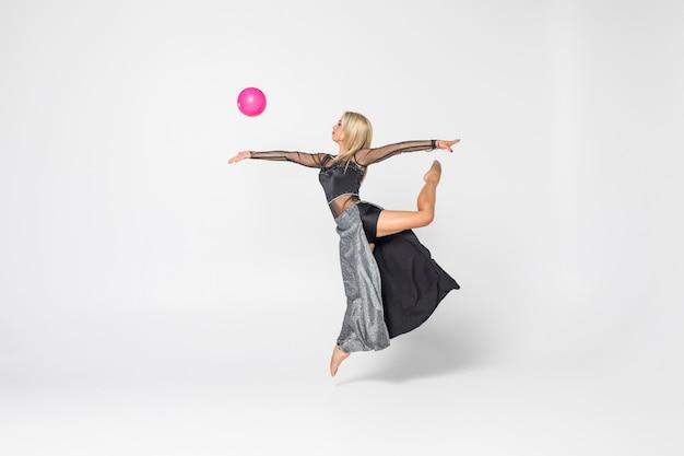Jovem garota está envolvida em ginástica art com bola isolada
