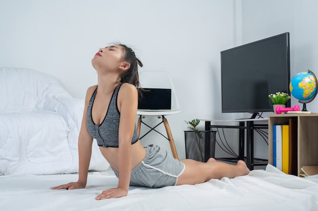 Jovem garota está malhando em casa, ela está praticando ioga em casa. conceito de vida saudável do vírus.