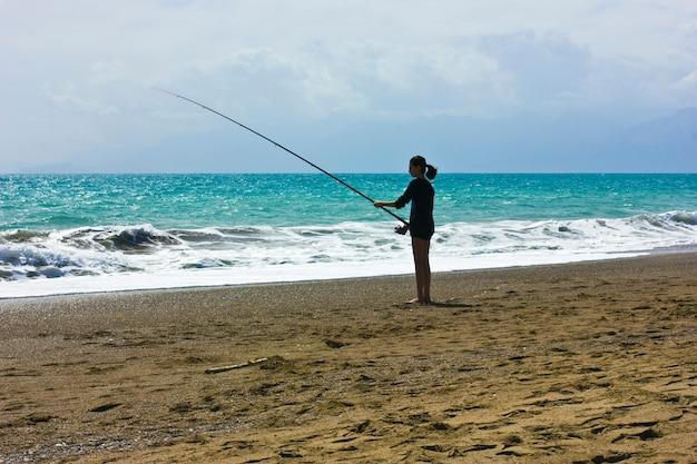 Jovem garota está pescando na praia, na costa do mar azul