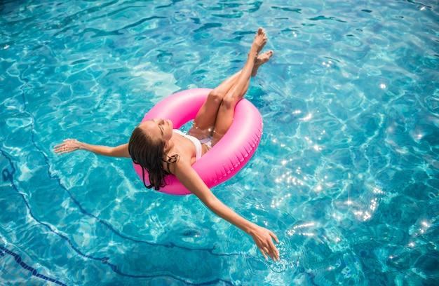 Jovem garota está relaxando na piscina com anel de borracha.