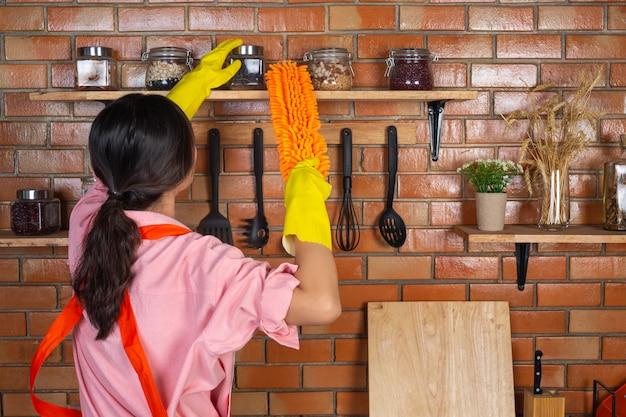 Jovem garota está usando luvas amarelas durante a limpeza da sala de cozinha com espanador em sua casa.