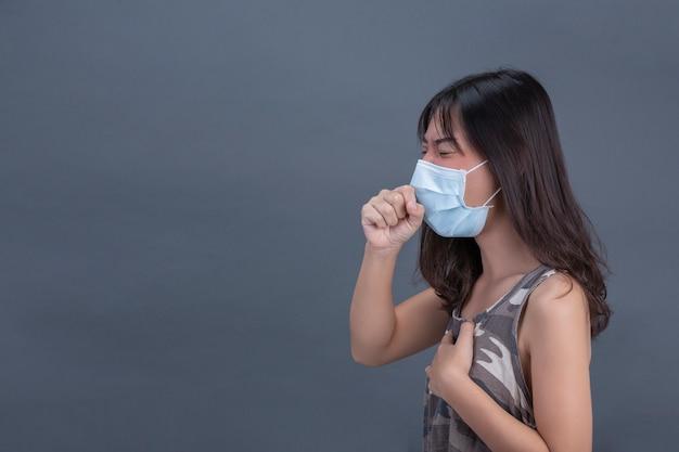Jovem garota está usando máscara enquanto tossindo na parede preta.