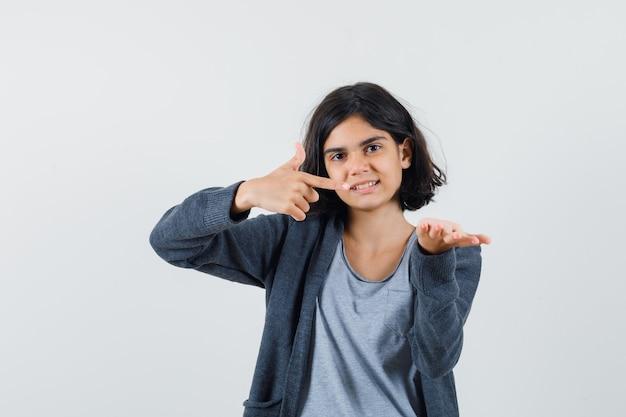 Jovem garota esticando uma mão enquanto segura algo e apontando para ela com o dedo indicador em uma camiseta cinza claro e um capuz cinza escuro com zíper frontal e está linda