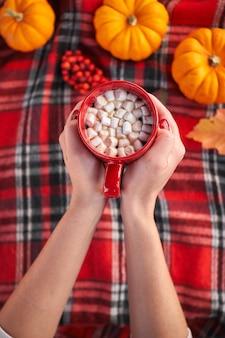 Jovem garota europeia com manicure vermelha nas unhas segurando uma xícara de café vermelha com marshmallows