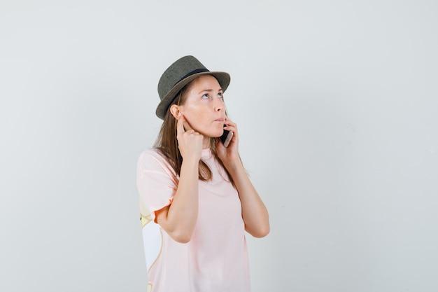 Jovem garota falando no celular em t-shirt rosa, chapéu e olhando pensativa, vista frontal.