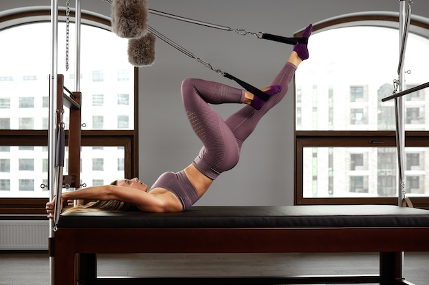 Jovem garota fazendo exercícios de pilates com uma cama reformadora. instrutor de fitness slim bonito em fundo cinza reformador, chave baixa, luz de arte. conceito de aptidão.