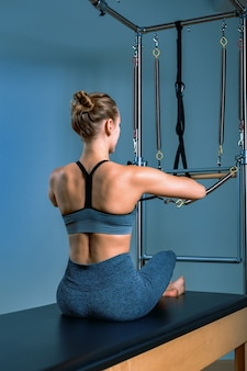 Jovem garota fazendo exercícios de pilates com uma cama reformadora. lindo instrutor de fitness fino na parede cinza reformador, discreto, luz artística. conceito de aptidão.