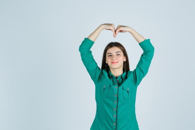 Jovem garota fazendo formato de coração com as mãos acima da cabeça na blusa verde, calça preta e olhando alegre, vista frontal.