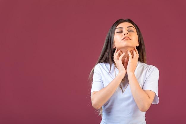 Jovem garota fazendo gestos sonhando ou rezando na mão no vermelho.