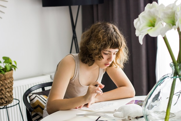 Jovem garota fazendo lição de casa na mesa branca. educação em casa e educação em casa