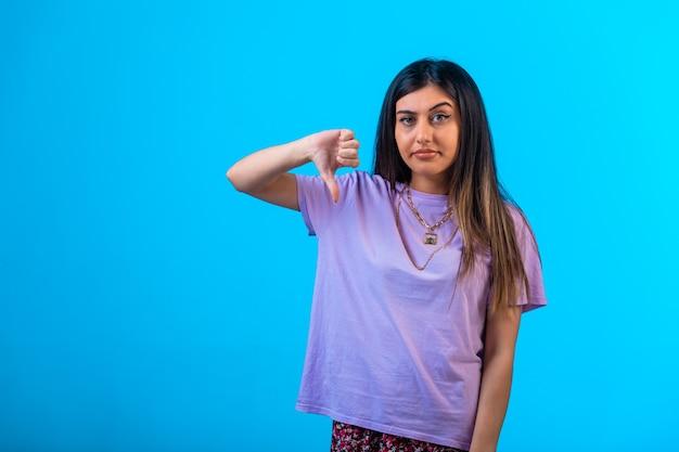 Jovem garota fazendo os polegares para baixo sinal com uma mão.