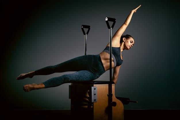 Jovem garota fazendo pilates exercícios com uma cama de reformador. instrutor magro bonito da aptidão no espaço cinzento do reformador, chave baixa, luz da arte. conceito de fitness