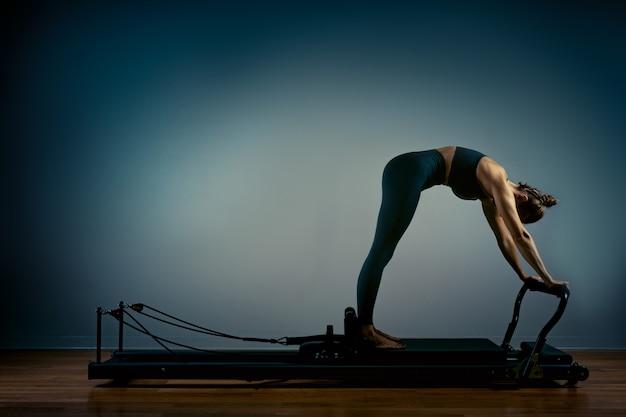 Jovem garota fazendo pilates exercícios com uma cama de reformador. instrutor magro bonito da aptidão no reformador