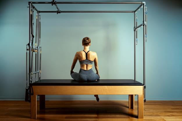 Jovem garota fazendo pilates exercícios com uma cama de reformador.