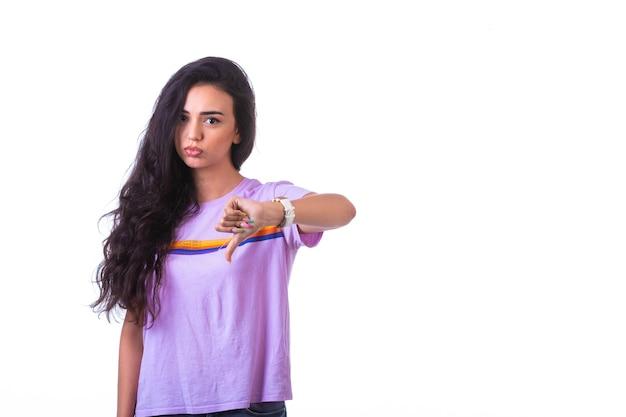 Jovem garota fazendo sinal de mão de antipatia em fundo branco.