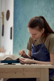 Jovem garota fazendo tigela de cerâmica em sala de aula. conceito de passatempo criativo