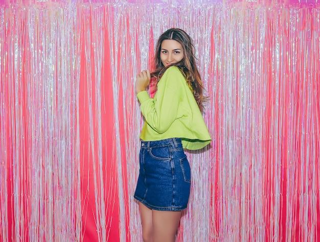 Jovem garota feliz no fundo de uma cortina rosa festiva em uma festa de aniversário