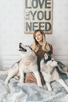 Jovem garota feliz no vestido marrom, sentado na cama e abraços adorável com sorridentes focinhos husky cachorros.