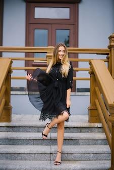Jovem garota feliz no vestido preto, sorrindo e feliz