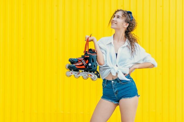 Jovem garota feliz segurando rolos na parede amarela