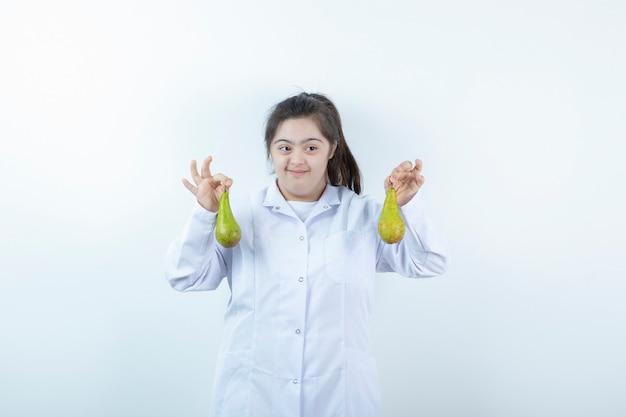 Jovem garota feminina com uniforme de médico segurando frutas de pêra.