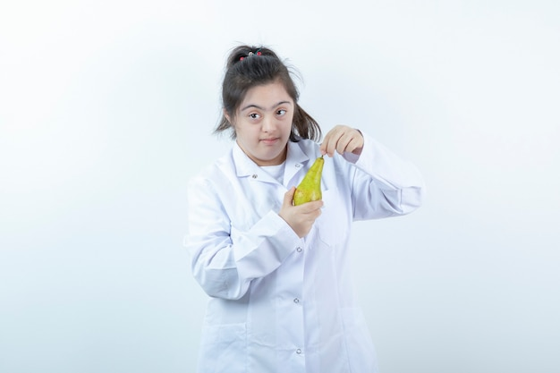 Jovem garota feminina em uniforme de médico, segurando a fruta da pêra.