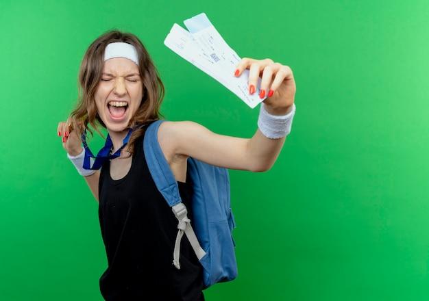 Jovem garota fitness em roupa esportiva preta com bandana e mochila mostrando passagens aéreas feliz e animada em pé sobre a parede verde