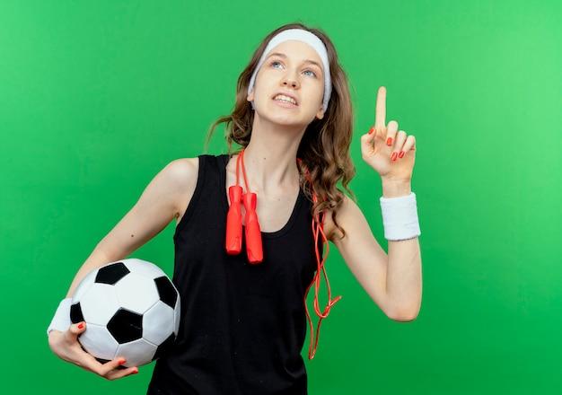 Jovem garota fitness em roupa esportiva preta com bandana e pular corda no pescoço segurando uma bola de futebol olhando para cima e mostrando o dedo indicador sorrindo sobre o verde
