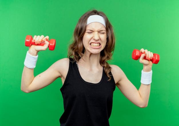 Jovem garota fitness em roupa esportiva preta com fita na cabeça, malhando com halteres parecendo tensa sobre o verde