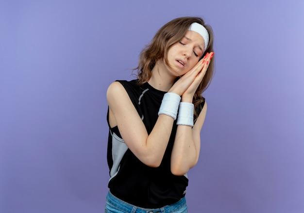 Jovem garota fitness em roupa esportiva preta com tiara segurando as palmas das mãos juntas, fazendo gesto de dormir, inclinando a cabeça nas palmas das mãos e quer dormir em pé sobre a parede azul