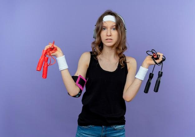 Jovem garota fitness em roupa esportiva preta com tiara segurando duas cordas de pular confusa em pé sobre a parede azul