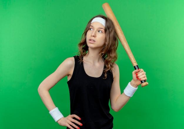 Jovem garota fitness em roupa esportiva preta com tiara segurando o taco basaball ouve a cabeça olhando para o lado com expressão pensativa em pé sobre a parede verde